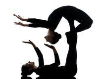 Schlangenmensch mit zwei Frauen, der gymnastisches Yogaschattenbild ausübt Stockfoto