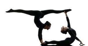 Schlangenmensch mit zwei Frauen, der gymnastisches Yogaschattenbild ausübt Stockfotos