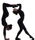 Schlangenmensch mit zwei Frauen, der gymnastisches Yogaschattenbild ausübt Stockbild