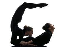 Schlangenmensch mit zwei Frauen, der gymnastisches Yogaschattenbild ausübt Lizenzfreies Stockfoto