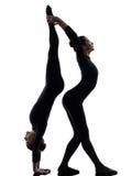 Schlangenmensch mit zwei Frauen, der gymnastisches Yogaschattenbild ausübt Stockbilder