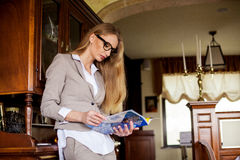 Schlanke attraktive blonde Stellung nahe dem Möbelstück mit der Zeitschrift in ihren Händen Tragender Anzug der Frau und Stockbild