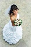 Schlanke Braut mit einem Blumenstraußblick aufwärts Stockbild