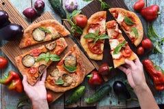 Schlanke Frau übergibt das Erreichen für gesunde vegetarische Pizza Homem Lizenzfreie Stockfotos