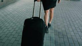 Schlanke Frauenbeine in den schwarzen hohen Absätzen beschuht das Gehen mit Reisegepäck stock video