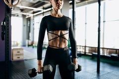 Schlanke junge Frau mit der Tätowierung, die in einer schwarzen Sportkleidung gekleidet wird, tut Übungen mit Dummköpfen in der T lizenzfreies stockbild