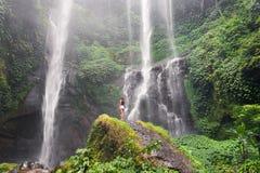 Schlanke Mädchenstellung vor einem Wasserfall auf einem Felsen lizenzfreie stockfotos
