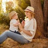 Schlanke schöne blonde Mutter in Jeans, in einem beige Hemd und in einem Hut h Stockfotos