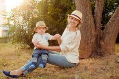 Schlanke schöne blonde Mutter in Jeans, in einem beige Hemd und in einem Hut h Lizenzfreie Stockfotos
