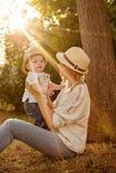 Schlanke schöne blonde Mutter in Jeans, in einem beige Hemd und in einem Hut h Lizenzfreies Stockfoto