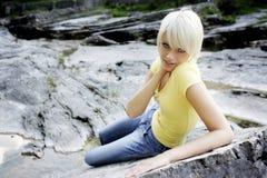 Schlanke schöne junge Frau, die auf einem Felsen sich entspannt Lizenzfreies Stockfoto