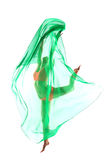 Schlanker junger Tänzer, der mit grünem Stoff springt Lizenzfreie Stockbilder