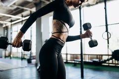 Schlanker Körper einer jungen Frau mit Tätowierung in einer schwarzen Sportkleidung, die Übungen mit Dummköpfen in der Turnhalle  lizenzfreie stockfotografie