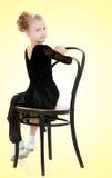 Schlanker kleiner Tänzer, der nahe dem alten Wien-Stuhl aufwirft Stockfoto