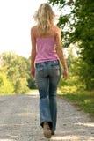 Schlankes blondes Gehen auf Kies-Straße Stockfotos