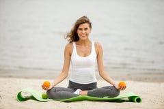 Schlankes Brünettemädchen hält Orangen in ihren Händen, die im Lotussitz auf einer Yogamatte auf sandigem Strand auf einem warmen stockbild
