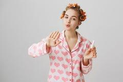 Schlankes gewöhnliches kaukasisches Mädchen in der gemütlichen Ausstattung, in tragenden roten Haarlockenwicklern und im Schlag a Lizenzfreies Stockfoto