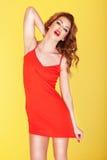 Schlankes junges Mädchen im roten Kleid stockfotografie