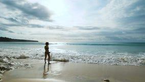 Schlankes Mädchen, das auf den sandigen Strand entlang der Küste des Ozeans geht, der die großen Wellen rollte Junge Frau fast stock footage