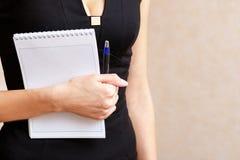 Schlankes Mädchen, das einen Notizblock und einen Stift hält stockfoto