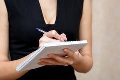 Schlankes Mädchen, das einen Notizblock und einen Stift hält lizenzfreies stockfoto