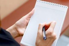 Schlankes Mädchen, das einen Notizblock und einen Stift hält stockbild