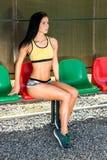 Schlankes Mädchen mit Sport erscheinen in den kurzen kurzen Hosen, sitzt auf einem Ben Lizenzfreies Stockbild