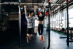 Schlankes Mädchen und athletische der Mann, die in der Sportkleidung gekleidet wird, ziehen auf der Stange in der Turnhalle hoch stockbild
