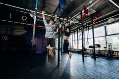 Schlankes Mädchen und athletische der Mann, die in der Sportkleidung gekleidet wird, ziehen auf der Stange in der Turnhalle hoch lizenzfreie stockfotos