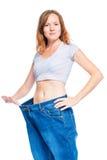 Schlankes rothaariges Mädchen, das alte Hosen nach verlierendem Gewicht zeigt lizenzfreies stockbild