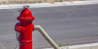 Schlauch und Schlüssel befestigt an einen roten Hydranten stockfoto