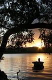 Schlauchboot auf Wasser am Sonnenaufgang Stockfotos