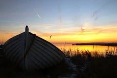 Schlauchboot silhouettiert bei Sonnenuntergang Lizenzfreies Stockbild