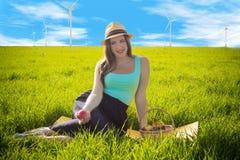 Schlauer Blick einer Schönheit in einem Kleid vor dem hintergrund der Windgeneratoren Lizenzfreies Stockbild