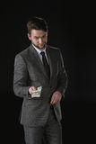 Schlauer Geschäftsmann, der die Dollarbanknoten lokalisiert auf Schwarzem gibt Stockfotos