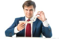 Schlauer Geschäftsmann, der Dollarschein aus Mausefalle heraus nimmt Stockfoto