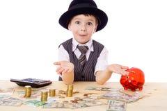 Schlauer Junge am Tisch mit Geld Stockbild