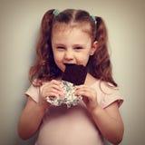Schlaues Kindermädchen, das dunkle Schokolade mit Vergnügen essen und neugierig lizenzfreies stockbild