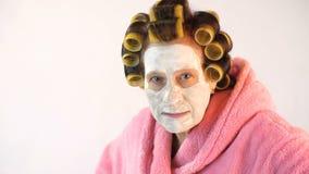 Schlechte Frau mit einer kosmetischen Maske und Lockenwicklern stock footage