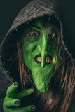 Schlechte Hexe, die einen Fluch unter ihrer Haube wirft Stockfotografie