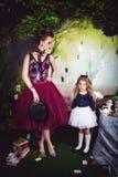 Schlechte Königin mit Magier Hut und Alice im Märchenland stockbild