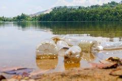 Schlechte Klimagewohnheit der unsachgemäßen Beseitigung nicht-biologisch abbaubarer PVCschalen und -flaschen in einem See Selekti lizenzfreie stockfotos