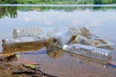 Schlechte Klimagewohnheit der unsachgemäßen Beseitigung nicht-biologisch abbaubarer PVCschalen und -flaschen in einem See Selekti stockbild
