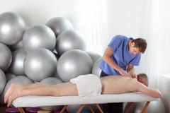 Schlechte Lage des Masseurs während der Massage Stockfoto