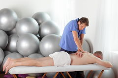 Schlechte Lage des Masseurs während der Massage Lizenzfreie Stockbilder