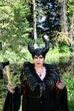 Schlechte Märchen, maleficent, boshafte Königin mit Hörnern und Krähe versehen Kleid mit Federn lizenzfreies stockfoto