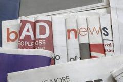 Schlechte Nachrichten auf Zeitungshintergrund Stockbilder