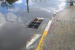 Schlechte Reparatur von Straßen Nach dem Regen läuft das Wasser nicht in den Abwasserkanal aus Lizenzfreies Stockfoto