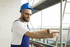 Schlechter Bauarbeiter in Arbeitsausstattung und im Sturzhelm steht an einer großen Höhe auf einer Baustelle mit Plänen Stockfoto