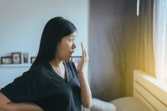 Schlechter Geruch, die Asiatin, die ihren Mund bedeckt und riechen ihren Atem mit den Händen stockbilder
